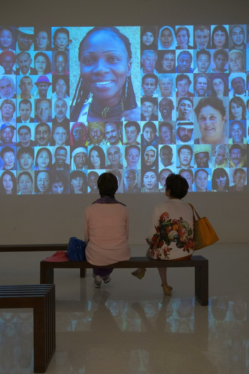 """Visitors watch the """"7 billion Others"""" video exhibit at the Museum of Photographic Arts in Balboa Park."""
