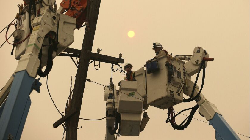 FILE - In this Nov. 9, 2018 file photo, Pacific Gas & Electric crews work to restore power lines in