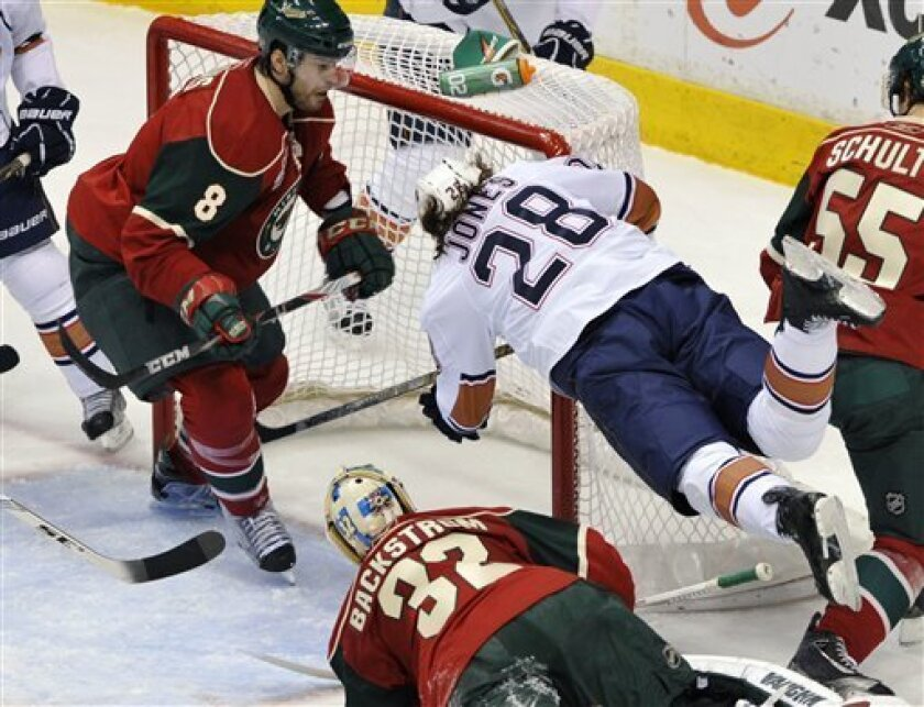 Edmonton Oilers' Ryan Jones (28) sails over Minnesota Wild goalie Niklas Backstrom (32), of Finland, while chasing the puck during the first period of an NHL hockey game on Thursday, March 31, 2011, in St Paul, Minn. Wild's Brent Burns (8) defends. AP Photo/Jim Mone)