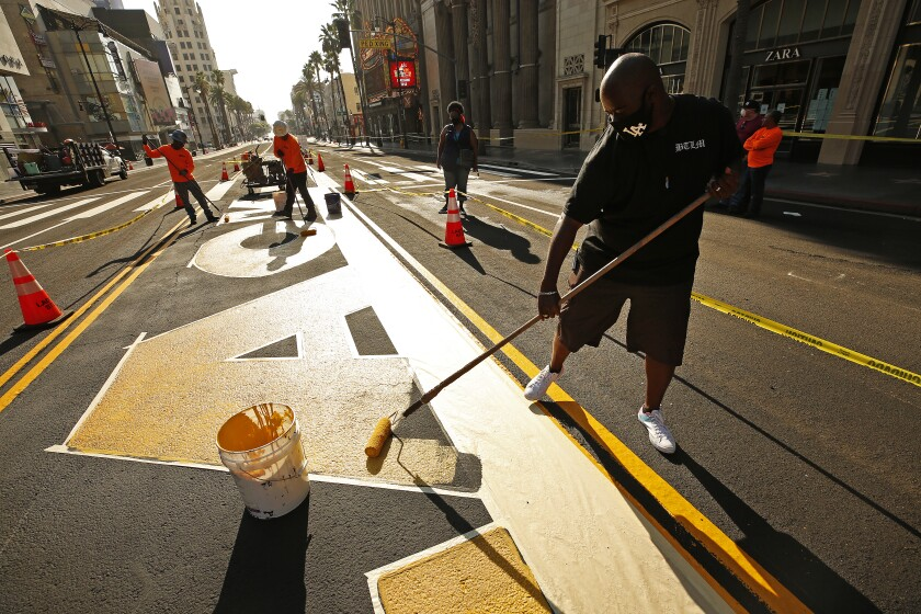 """Designer Lucky Alexander Fuller rolls yellow paint down on the first letters of the permanent """"All Black Lives Matter."""""""