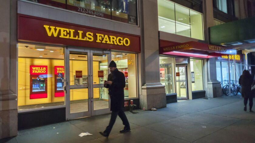 A pedestrian walks by a Wells Fargo & Co. branch in New York City.