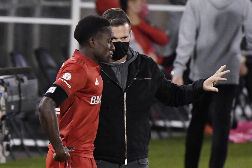 Toronto FC head coach Greg Vanney, right, talks with Richie Laryea during the first half of an MLS soccer match against the New York Red Bulls, Wednesday, Oct. 14, 2020, in East Hartford, Conn. (AP Photo/Jessica Hill)