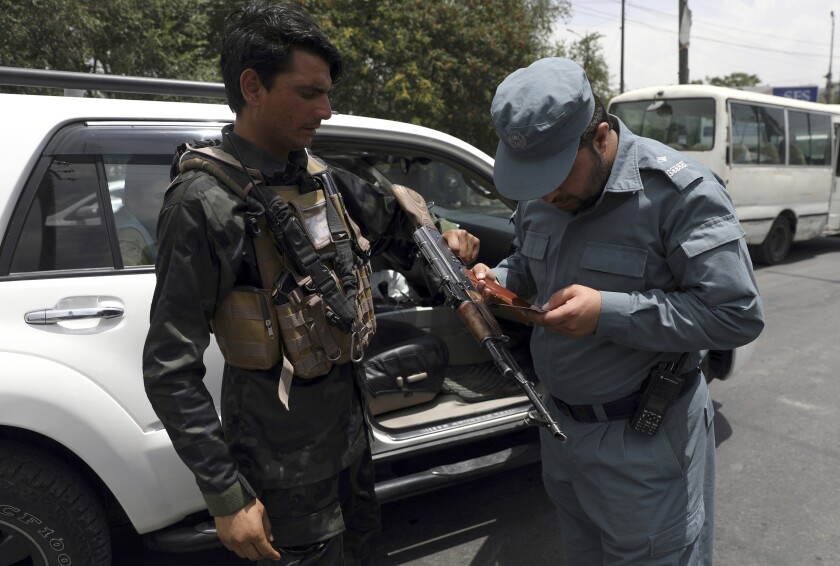 An Afghan policeman checks the documentation of a gun owner, at a temporary checkpoint in Kabul, Afghanistan, Sunday, July 4, 2021. Long before the last U.S. and NATO troops packed up to leave Afghanistan, American diplomats arriving in the capital Kabul were taken to the heavily fortified U.S. Embassy by helicopter. The short four- mile road trip through Kabul's chaotic traffic was considered too dangerous. (AP Photo/Rahmat Gul)