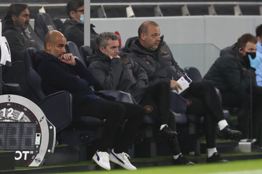 Manchester City's head coach Pep Guardiola sits on the bunch during the English Premier League soccer match between Tottenham Hotspur and Manchester City at Tottenham Hotspur Stadium in London, England, Saturday, Nov. 21, 2020. (Clive Rose/Pool via AP)