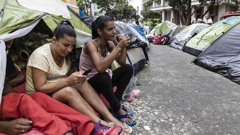 Women prepare to leave for work after their building, the Wilton Paes de Almeida, burned May 1.