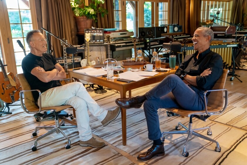 Springsteen and Obama sit at a table; in the background are guitars and recording equipment.
