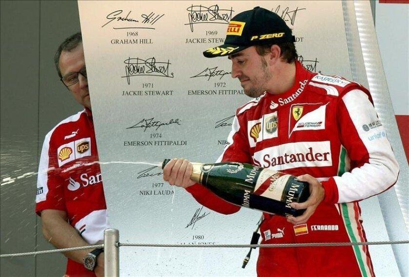 El piloto español de Ferrari Fernando Alonso celebra en el podio en presencia del director de equipo, Stefano Domenicali, su victoria en el Gran Premio de España. EFE/Archivo