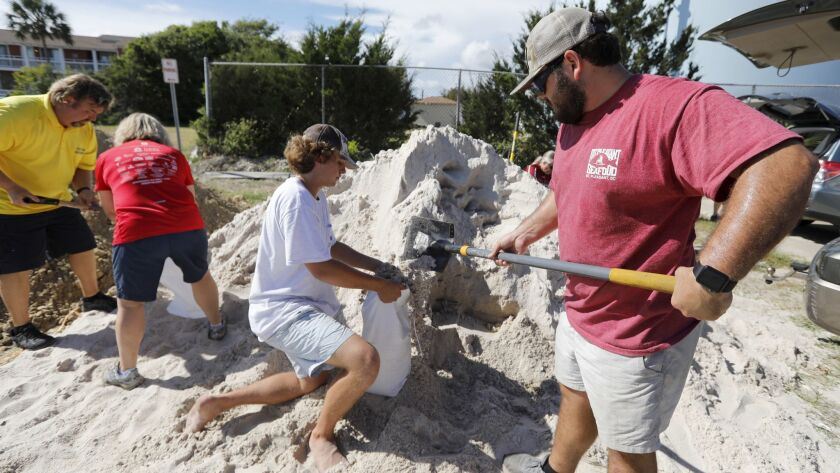 Walker Townsend, at right, from the Isle of Palms, S.C., fills a sand bag while Dalton Trout, in cen