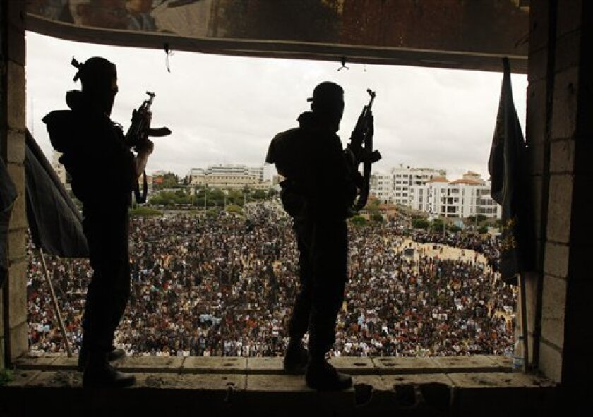 """Palestinian militants from the Islamic Jihad stand guard during a rally in Gaza City , Friday, Oct. 30, 2009. Tens of thousands of Islamic Jihad loyalists gathered in Gaza in a memorial to the militant group's founder. Holding plastic models of rockets and wearing masks and mock suicide bomber's vests, the members chanted """"death to Israel"""", """"Mohammed's army will be back to wipe off the Hebrew state."""" (AP Photo/Hatem Moussa)"""