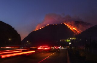 LOS ANGELES TIMES Traffic continues as flames roar up a steep hillside near the Getty Center in Los Angeles. The blaze forced evacuations and has burned more than 600 acres.
