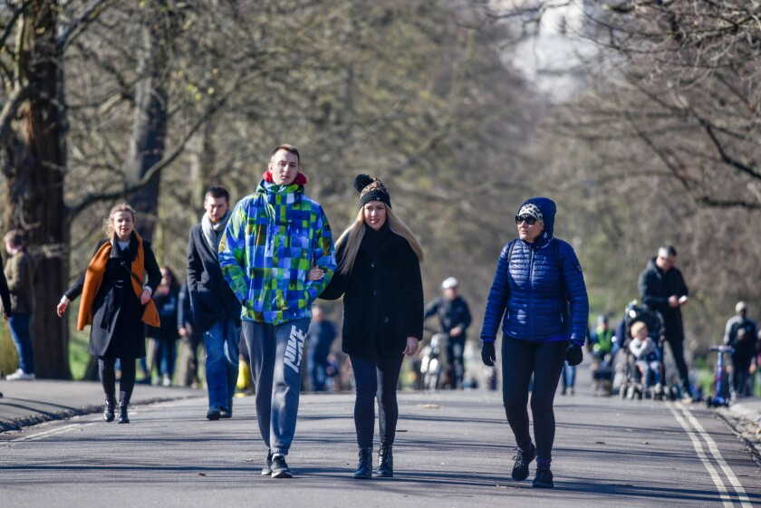 People are seen walking in Greenwich Park in London on Sunday.