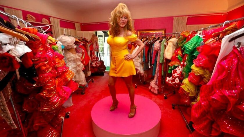 Charo vamps in her home's pink room, which is filled with her eye-popping stage attire.