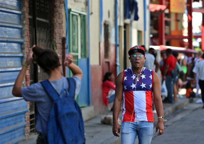 Un hombre vestido con una camiseta con la bandera de EEUU camina por una calle de La Habana (Cuba). EFE/Archivo