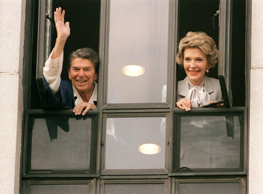 (FILES) This file photo taken on January 06, 1987 shows US President Ronald Reagan waving to the press from the window of his room at Bethesda Naval Hospital with First Lady Nancy Reagan.Nancy Reagan died March 6, 2016, at age 94, a spokeswoman for the Reagan Presidential Library and Foundation in