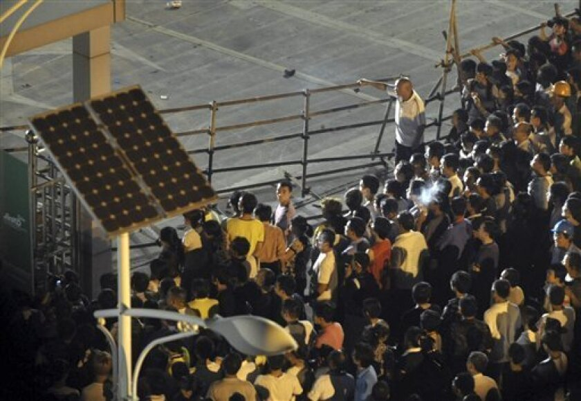 In this photo taken Saturday Sept. 17, 2011, villagers gather in protest outside the gates to solar panel manufacturer Zhejiang Jinko Solar Co. Ltd. in Hongxiao village in Haining city in eastern China's Zhejiang province.   Hundreds of villagers have been demonstrating in recent days against pollu