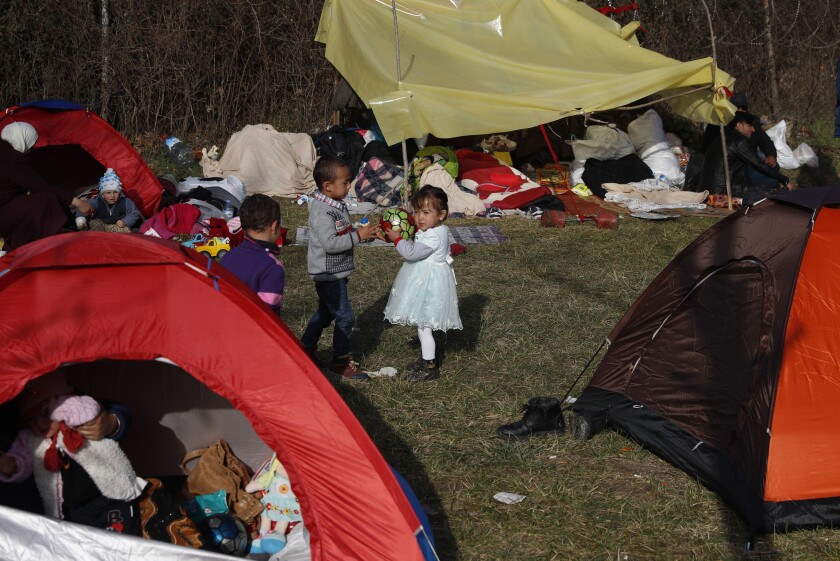Children play as migrants gather in a field in Edirne, near the Turkish-Greek border on Sunday, March 8, 2020. Thousands of migrants headed for Turkey's land border with Greece after President Recep Tayyip Erdogan's government said last week that it would no longer prevent migrants and refugees from crossing over to European Union territory. (AP Photo/Darko Bandic)