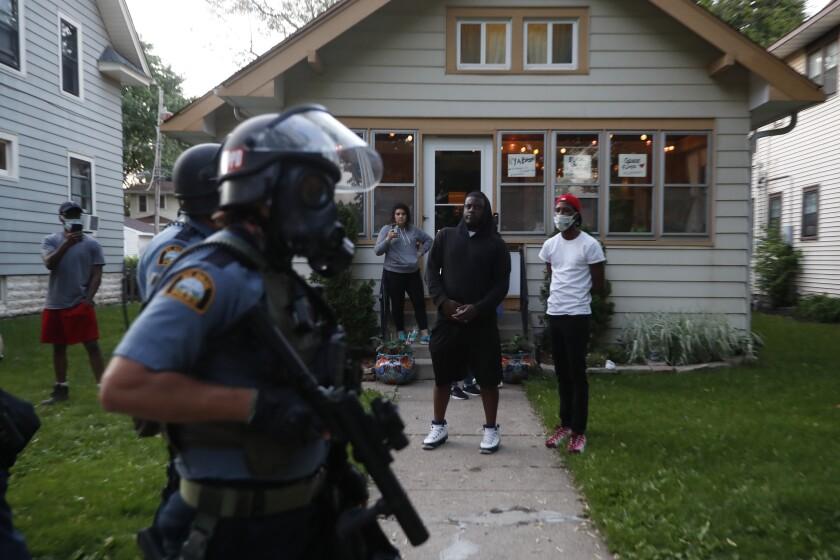 Bystanders watch as police walk down a street in St. Paul, Minn.