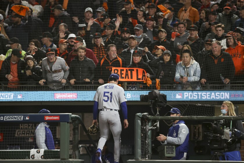 San Francisco Giants fans hold signs and taunt L.A. Dodgers reliever Alex Vesia as he leaves a game
