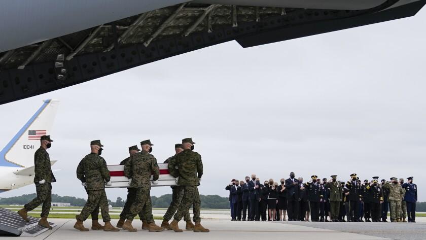 سربازان در پایگاه هوایی دوور یک جلد پوشیده از پرچم حمل می کنند.