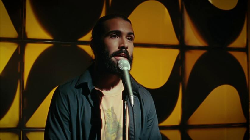 """Gonzalo Trigueros standing at a microphone in """"Such a Funny Life."""""""