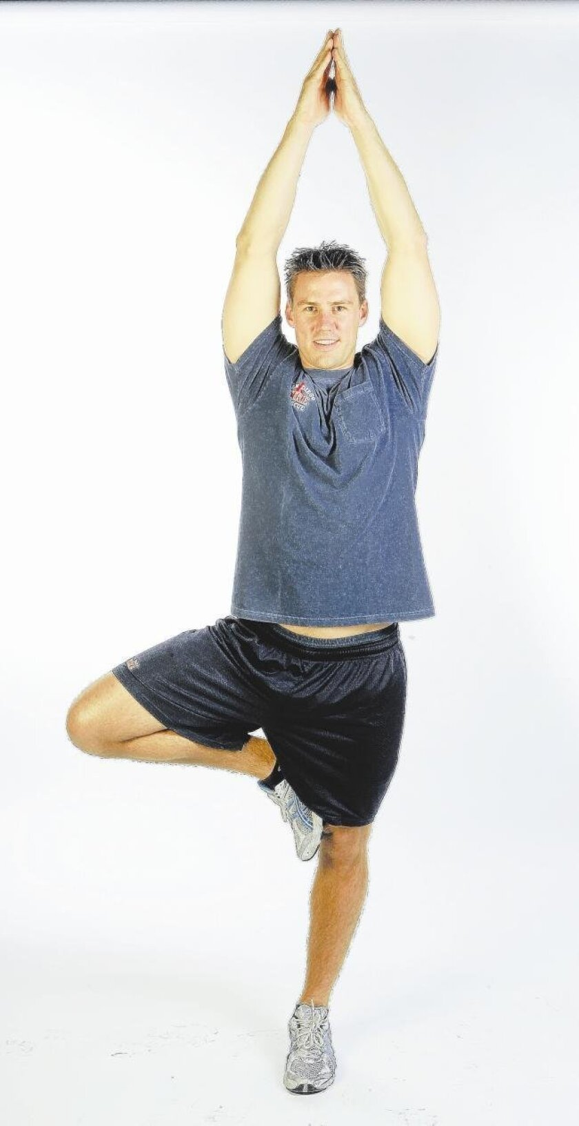 San Diego fire engineer Stephen Laughlin works on core stability, balance and hip flexibility as he demonstrates a traditional yoga tree pose.
