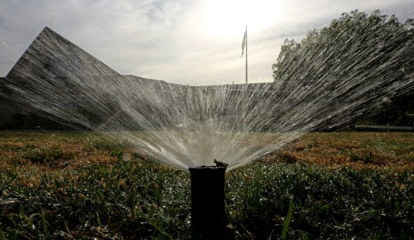 FILE - In this July 15, 2014, file photo, sprinklers water a lawn in Sacramento, Calif. Most Californians have heard by now that they should stop watering their lawns to save water in the drought. But there are smaller steps to take, too, from taking shorter showers and doing less laundry to restau