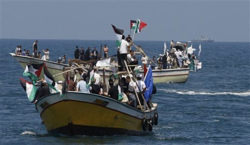 Palestinians ride boats in Gaza waters and an Israeli navy vessel patrols, background, as a flotilla of aid ships leaves for the blockaded territory, in Gaza city, Sunday, May 30, 2010. Hundreds of pro-Palestinian activists on seven ships were to set sail for the Gaza Strip on Sunday from internati