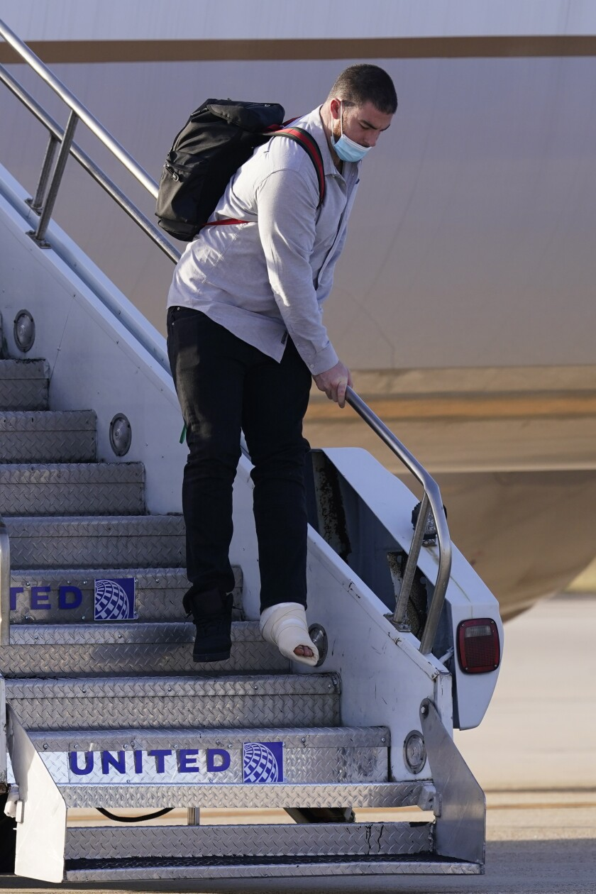 Kansas City Chiefs left tackle Eric Fisher gets off the plane with his teammates ahead of the NFL Super Bowl 55 football game against the Tampa Bay Buccaneers, Saturday, Feb. 6, 2021, in Tampa, Fla. Fisher tore his Achilles tendon during the AFC Championship against the Buffalo Bills. (AP Photo/Charlie Riedel)