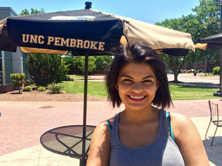 In this May 24, 2016 photo. Kristy Hunt, a 21-year-old business and marketing major, studies outside the University of North Carolina at Pembroke bookstore on the first day of summer classes in Pembroke, N.C. Hunt says a North Carolina Senate proposal to reduce tuition at UNCP to $500 a semester fo