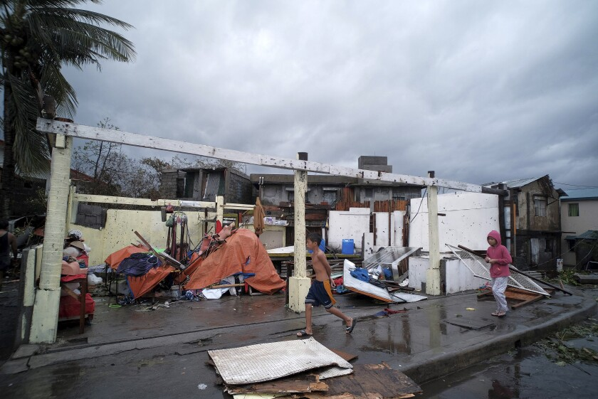Children pass by homes damaged by strong winds as Typhoon Kammuri slammed Legazpi city in the province of Albay, southeast of Manila, on Tuesday.