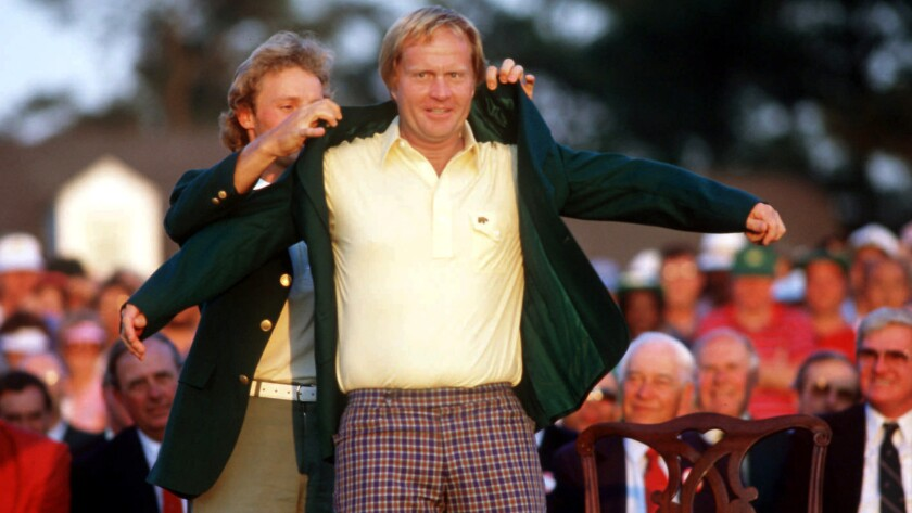 Bernhard Langer helps Jack Nicklaus slip into the winner's green jacket after he triumphed at the Masters in 1986.