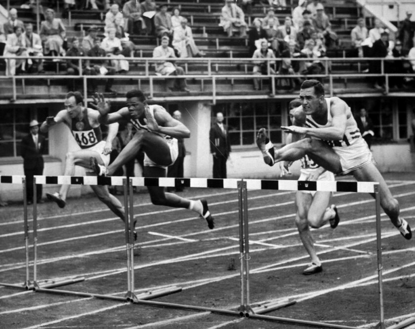 This July 26, 1952 file photo shows Milt Campbell, center, of Plainfield, N.J., getting set to clear the final hurdle to make him the winner in the fifth heat of the 110-meter hurdles event in the Olympic decathlon at Helsinki, Finland. Campbell, who became the first black to win the Olympic decathlon in 1956 and went on to play professional football and become a motivational speaker, died Nov. 2, 2012, after a battle with prostate cancer. He was 78.