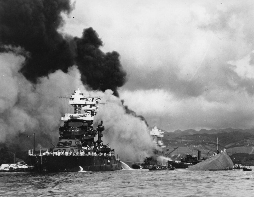 Part of the hull of the capsized battleship Oklahoma is seen at right as the battleship West Virginia (center) begins to sink after suffering heavy damage, while the battleship Maryland (left) is still afloat on Dec. 7, 1941, in Pearl Harbor, Oahu, Hawaii.