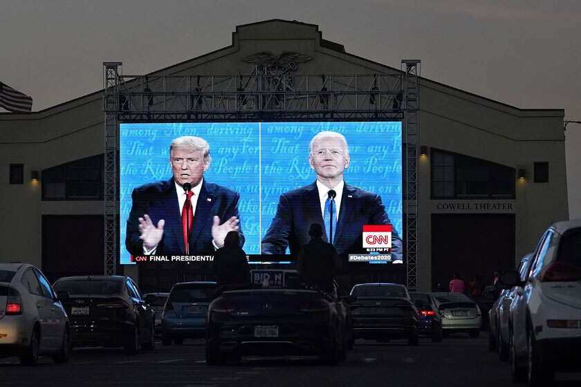 President Trump and Joe Biden appear at last week's debate on a large screen at a drive-in watch party in San Francisco.