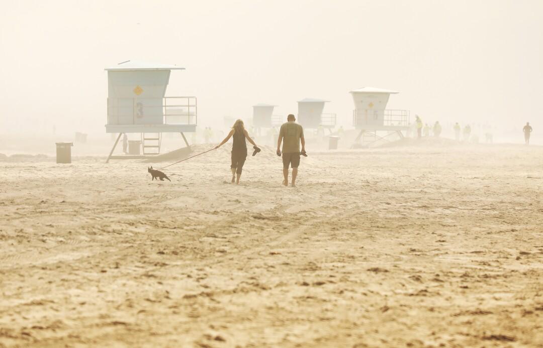 People walk the beach under partly cloudy skies atHuntington Beach