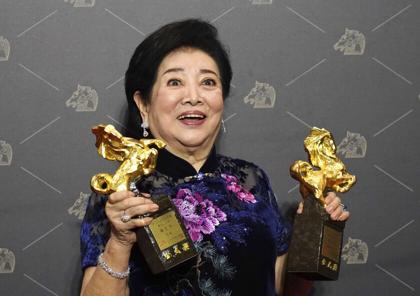 Taiwanese actress Chen Shu-fang holds her awards for leading actress and supporting actress at the 57th Golden Horse Awards