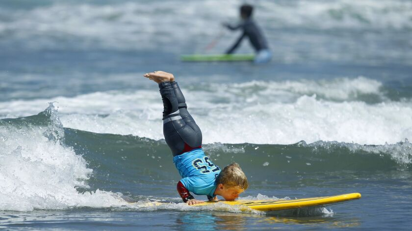 Sebastian Desposato, 9, does a handstand during the Junior Sea Foundation youth Adaptive Surfing Camp in Del Mar on Thursday. Sebastian, who has a form of dwarfism called achondroplasia, was working on some new moves for the Switchfoot Bro-Am tournament Saturday in Encinitas.