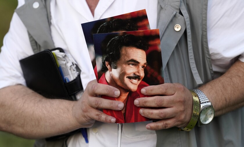 A guest holds programs during the unveiling of a memorial sculpture of the late actor Burt Reynolds at Hollywood Forever Cemetery, Monday, Sept. 20, 2021, in Los Angeles. Reynolds died in 2018 at the age of 82. (AP Photo/Chris Pizzello)
