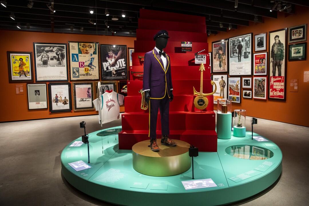 Una pasarela con una modelo con un traje morado, un cajón rojo con la guitarra de Prince, una camiseta y una pequeña figura.