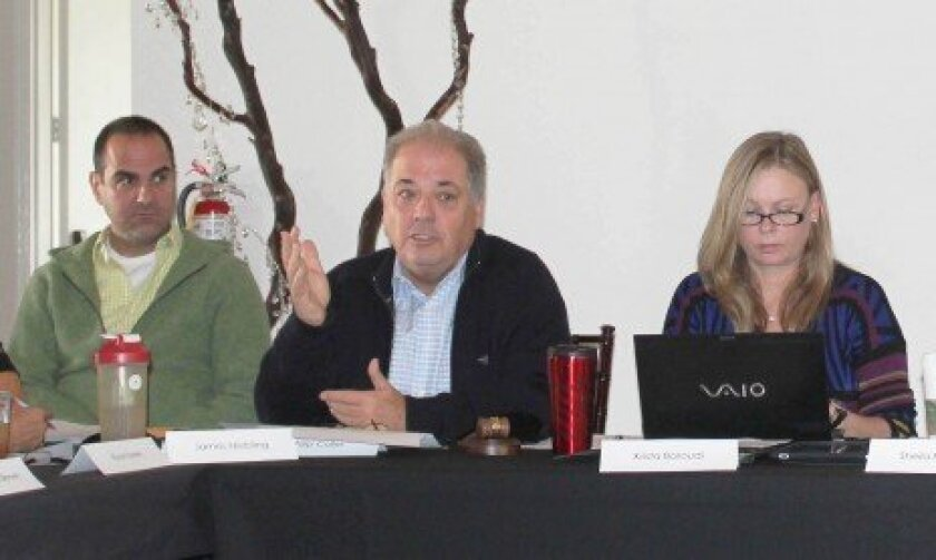 La Jolla Village Merchants Association past board president Phil Coller (center) outlines difficulties the association faced in realizing its mission during his three-year tenure. Board members, including James Niebling (left) and secretary Krista Baroudi, listen in.