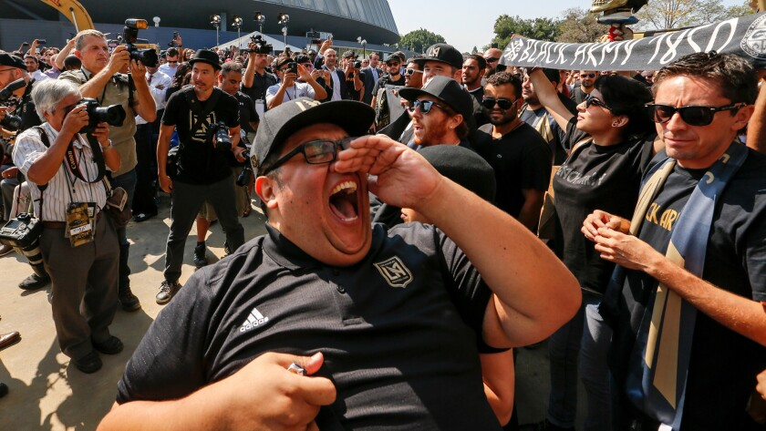 """Francisco """"Tiny"""" Picos leads a cheer by the Black Nation soccer fans for the Los Angeles Football Club  before the ground breaking and naming rights  ceremony."""