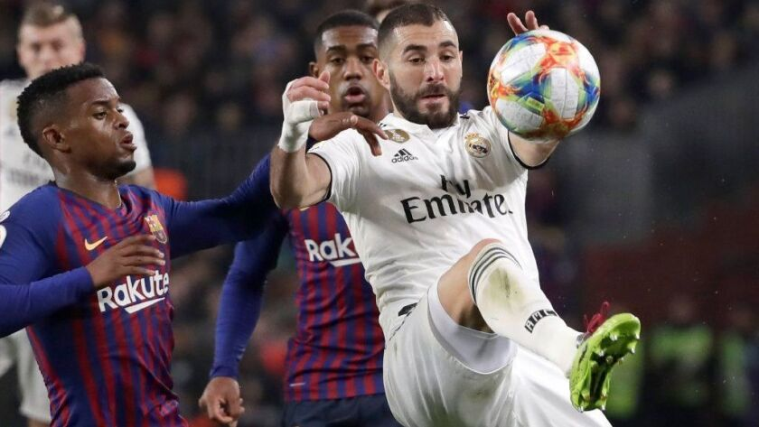 Real Madrid forward Karim Benzema controls the ball in front of Barcelona defender Nelson Semedo, left, during a Copa del Rey semifinal match on Wednesday.