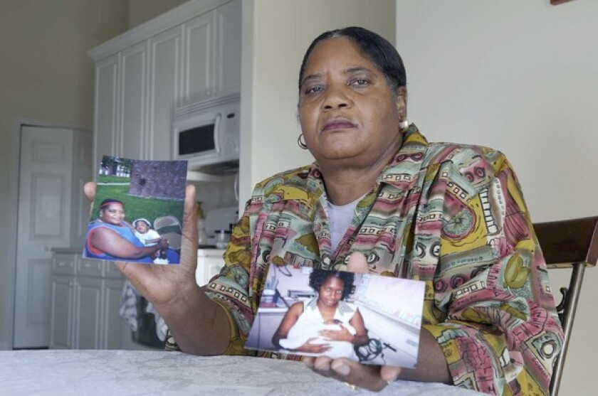 Helen Brown holds a photo of grandson Thierry LaMarque Jr., left, and one of his mother, Glenda Brown.