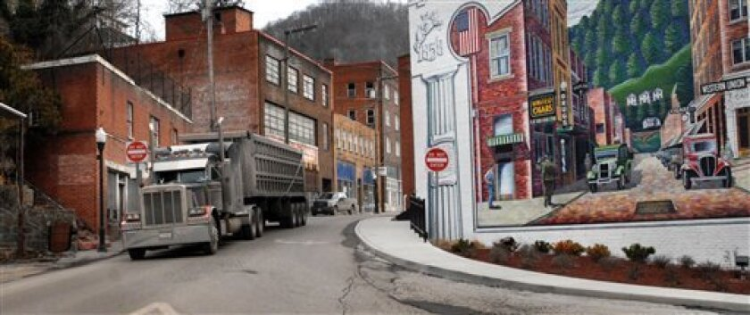 FILE - In this Feb. 9, 2011, file photo, a coal truck drives out of downtown Welch, W.Va. A record number of U.S. counties _ more than 1 in 3 _ are now dying off, hit by an aging population and weakened local economies that are spurring young adults to seek jobs elsewhere. New 2012 census estimates