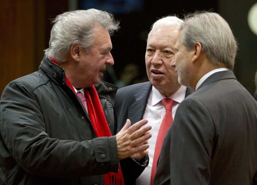 Spanish Foreign Minister Jose Manuel Garcia-Margallo, center, speaks with Luxembourg's Foreign Minister Jean Asselborn and EU Commissioner for Enlargement Johannes Hahn during a meeting of EU foreign ministers at the EU Council building in Brussels on Monday, Feb.15, 2016. European Union officials