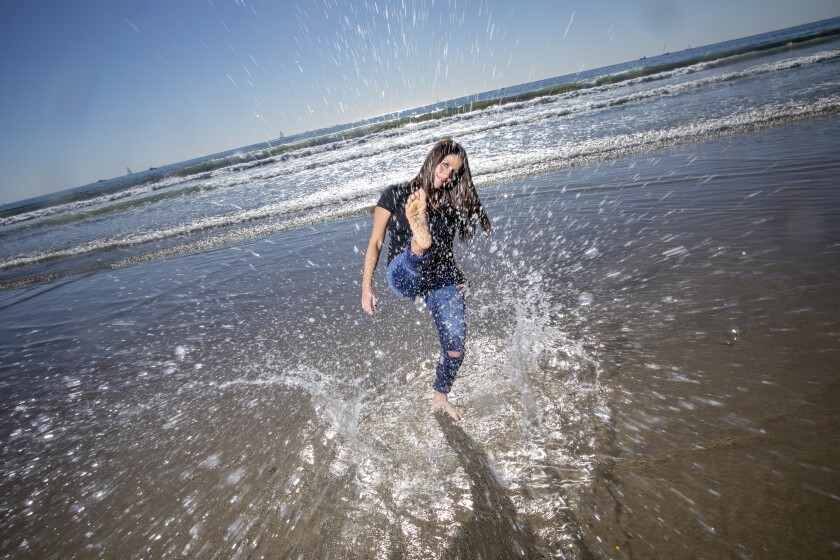 A woman splashes water up with her foot at the ocean's edge