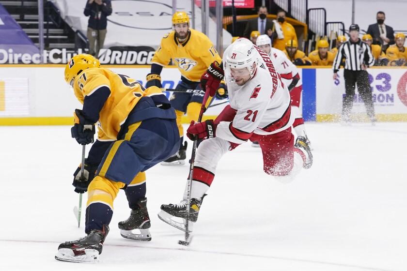 Carolina Hurricanes right wing Nino Niederreiter (21) shoots as Nashville Predators' Dante Fabbro (57) defends in the third period of an NHL hockey game Tuesday, March 2, 2021, in Nashville, Tenn. (AP Photo/Mark Humphrey)