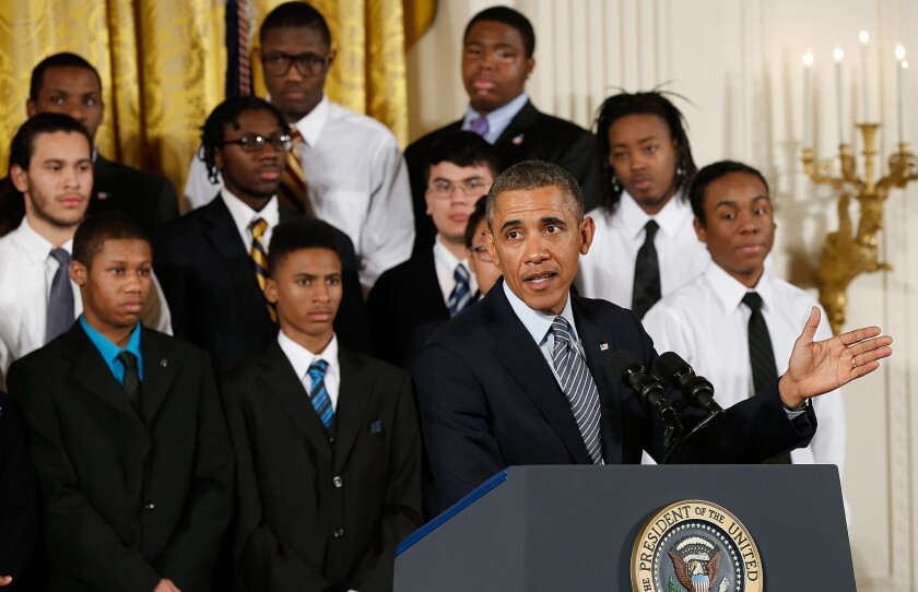 President Obama speaks as young men who participate in the Becoming A Man program in Chicago watch during a Feb. 27 event in the East Room of the White House. Obama signed an executive memorandum following remarks on the My Brother's Keeper initiative.