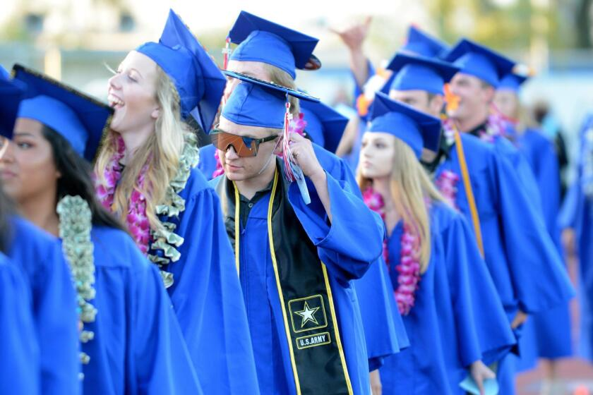 A student adjusts his tassel as classmates check the stands for familiar faces.