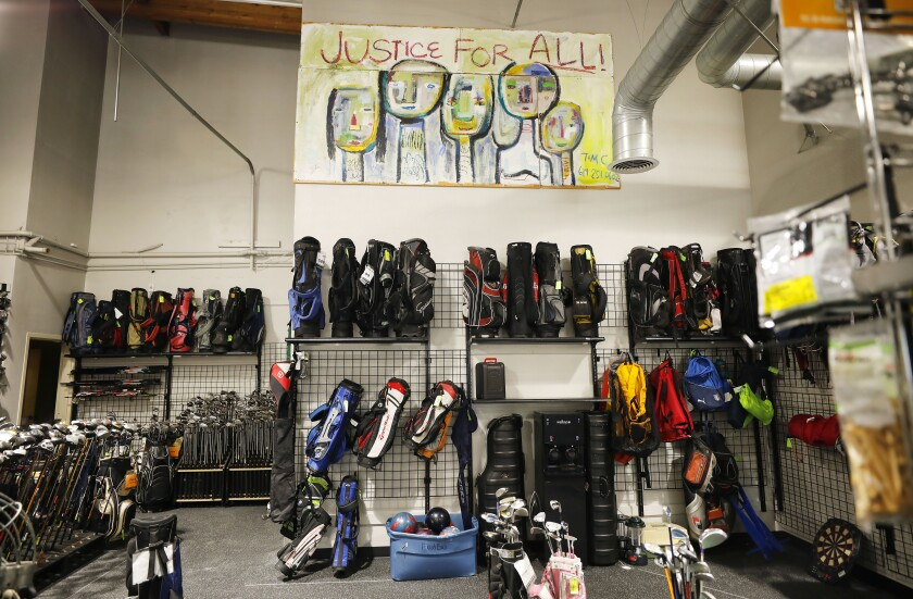A mural that says Justice For All hangs in Play It Again Sports.